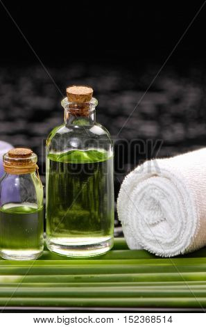 tranquil spa scene- towel with black stones with candle ,green plant
