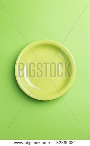Green plate on green background above view.Useful as a food background