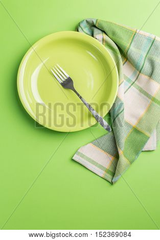 Green plate with fork and napkin on green background above view
