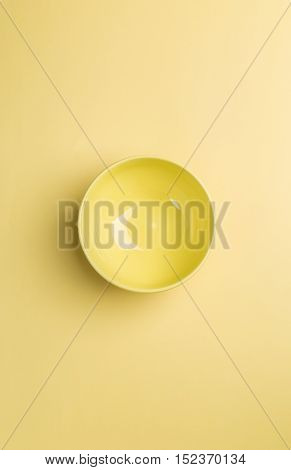Yellow bowl on yellow background above view.Useful as a food background
