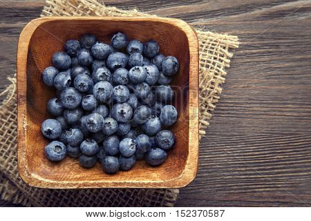heap ripe sweet blueberries on wooden table top view