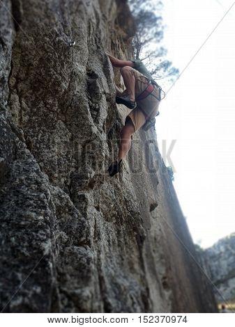 rock climbing shown by climber climbing a granite quarry wall