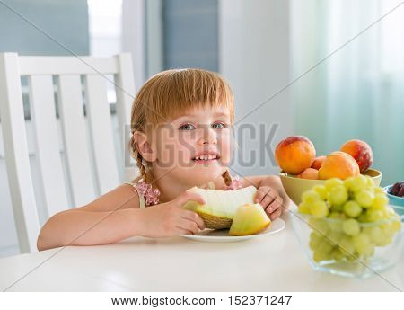 cute little girl taking water melon with fruits on the table