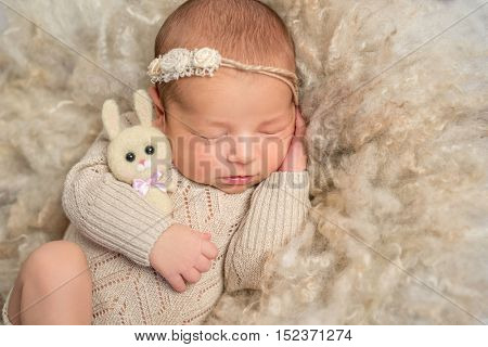 portrait of sweet sleeping newborn girl in jumpsuit with toy hare on fluffy blanket