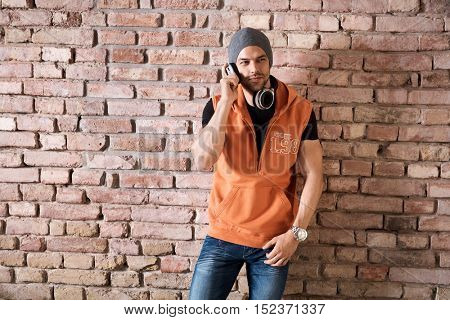 Young man in cap standing at brick wall listening music on headphone.