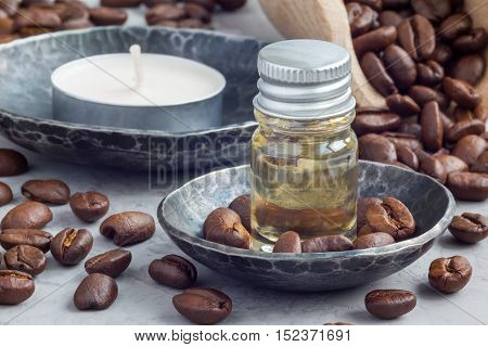 Coffee essential oil in a glass bottle on background with coffee beans. Horizontal close-up