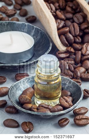 Coffee essential oil in a glass bottle on background with coffee beans. Vertical close-up