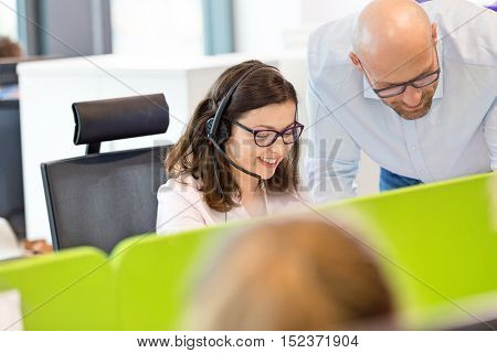 Mid adult businessman assisting female operator in office