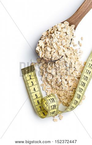 Diet concept. Dry rolled oatmeal and measuring tape.