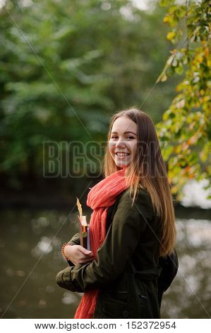 Autumn. Lovely girl in a bright red scarf walks in autumn park. Trees reflected in the pond. Through foliage the sunlight makes the way. In the hands of a girl is notebooks. She smiles.