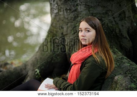 Cute girl sitting against a backdrop of a huge old tree. A bright red scarf attracts attention. On a lap at the girl the open notebook lies. She looks into the camera and smiles.