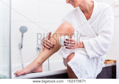 Woman in bathroom sitting at edge of bathtub putting on lotion on legs