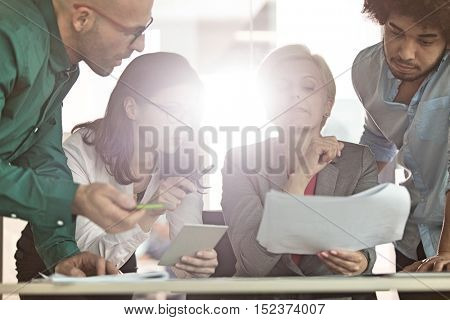 Multi-ethnic business people having discussion at table in office