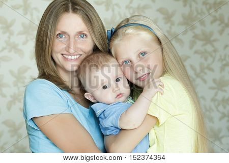 Family of three smiling and hugging people indoor day portrait