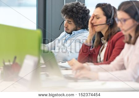 Tired male customer service representative with colleagues working in office