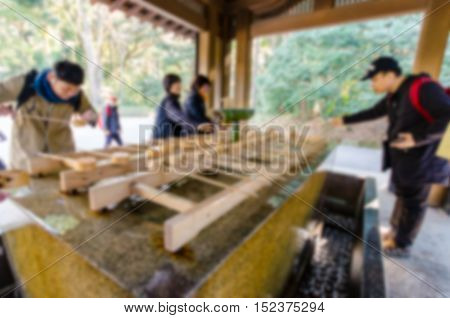 Blurred background . Unidentified people rinse hands and mouth at Temizuya. Temizuya is a Shinto water ablution pavilion for a ceremonial purification rite known as temizu.