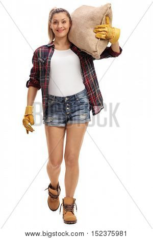 Full length portrait of a happy female farmer walking and carrying a burlap sack isolated on white background