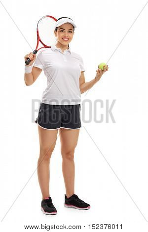 Full length portrait of a female tennis player posing with a racket and a tennis ball isolated on white background