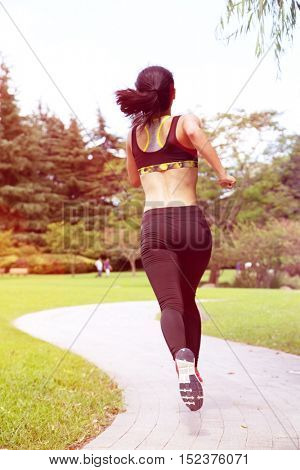 Rear view of woman running in park