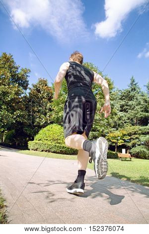 Low angle rear view of caucasian man running in park
