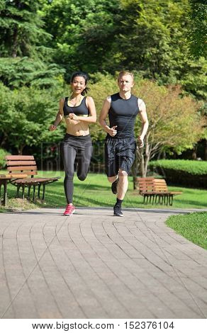 Multi ethnic couple running in park