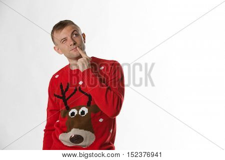 Caucasian man with hand on hips whilst wearing a christmas jumper thinking