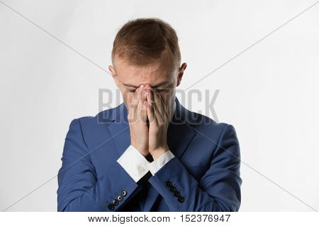 Businessman with holding his head in hands in shame