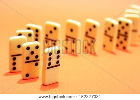 White dominoes standing in a row on yellow background
