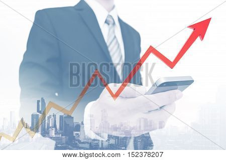 Businessman using smartphone with rising up arrow, representing business growth