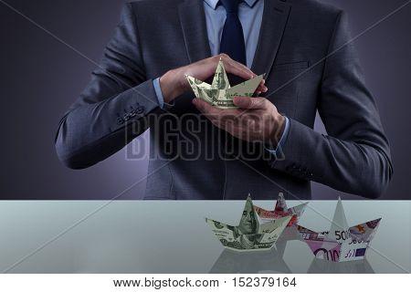 Businessman holding dollar paper boats