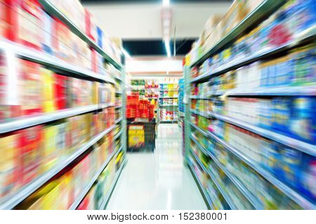 The shelves of goods on both sides of the supermarket aisle.