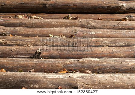 Bridge surface over mountain forest river of rough pine wood logs closeup as background