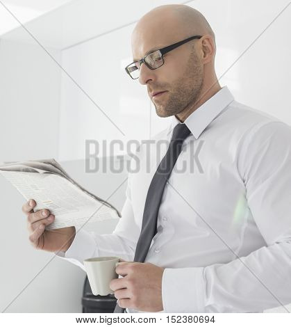 Mid adult businessman having coffee while reading newspaper