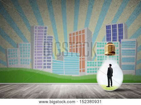 Businessman inside light bulb against city drawn concept