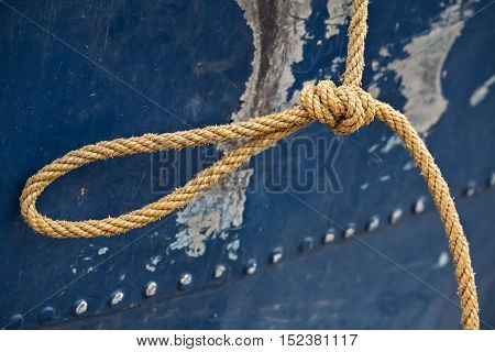 Closeup og a knot and thick stron rope on an old fishin boat