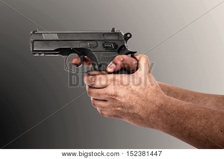 Hand holding a gun isolated on grey background