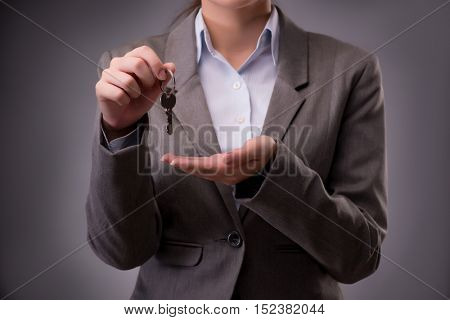 Woman holding keys in housing mortgage concept