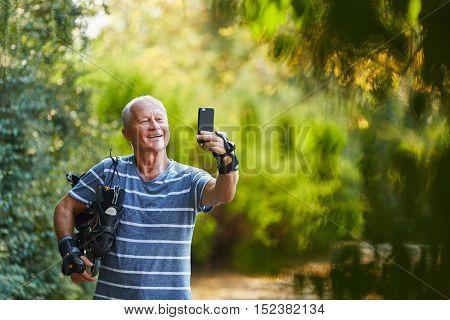 Happy senior man in inline skates taking a selfie in the nature