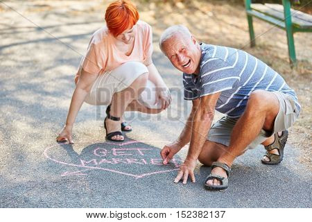 Senior couple in love drawing a hear on the floor as a declaration of love