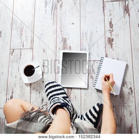 Woman with tablet,  cup of coffee, notepad at home. Woman is a daily routine