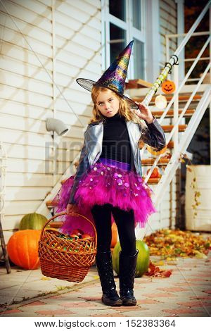 Beautiful little girl in a costume of witch celebrating halloween. Trick or treat. Halloween party.