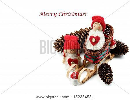 Christmas Decoration Concept with Handmade Dolls in Knit Hats Fir Cones Sleigh and Inscription closeup on White background