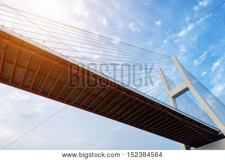 Big suspension bridge in beams of the coming sun against the blue sky