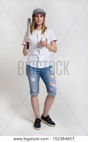 Young attractive woman with a baseball bat and ball. Cool girl in ragged shorts, shirt and a baseball cap. A girl holding a bat on his shoulder.