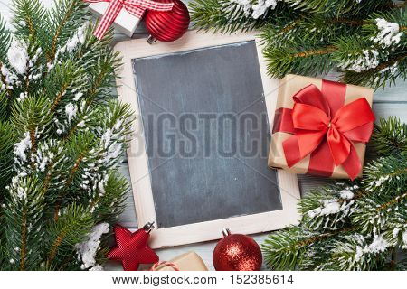 Christmas chalkboard, decor, gift box and fir tree on wooden table. Top view with copy space for your text