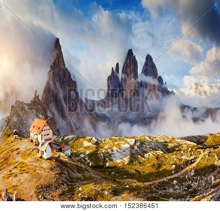 Great sunny view of the National Park Tre Cime di Lavaredo with rifugio Locatelli. Dolomites, South Tyrol. Location place Auronzo, Italy, Europe. Tourist attraction. Dramatic cloudy sky. Beauty world.