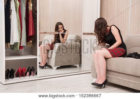 Young woman choosing clothing for evening party