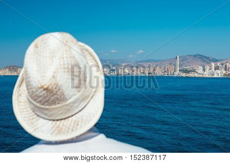 Back view of unrecognizable person in straw hat standing against seascape