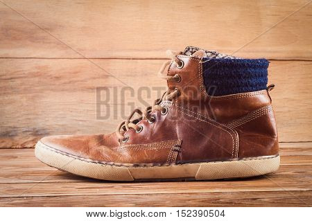 Old brown sneakers on wood background. Fashion background