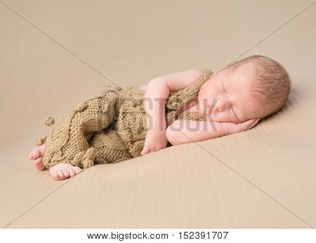 beautiful newborn baby in knitted overalls sleeping on blanket with hand under his head